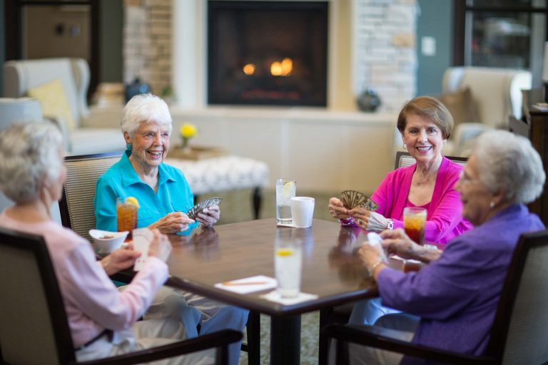Four residents play bridge in Taproot, one of the many amenities at The Forest.