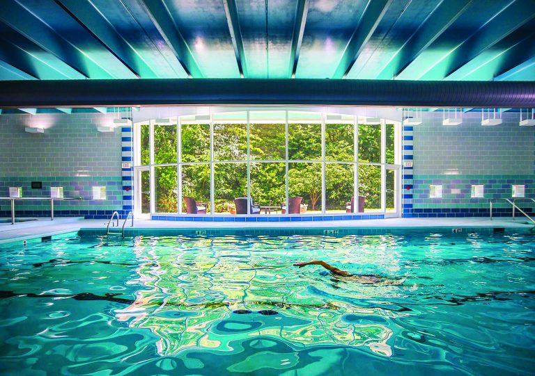 woman swimming in deep blue and green indoor pool with floor to ceiling windows