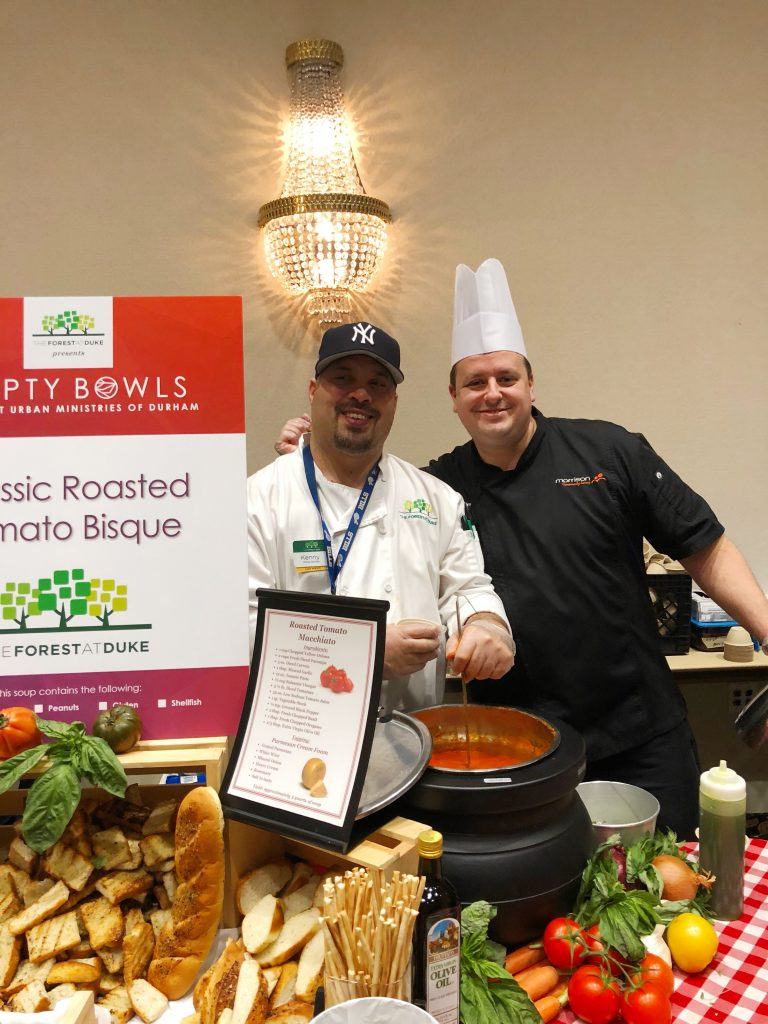 Two men smiling at Urban Ministries, one in a baseball cap and one in a white chefs hat, in front of a table with large bowls of soup and bread