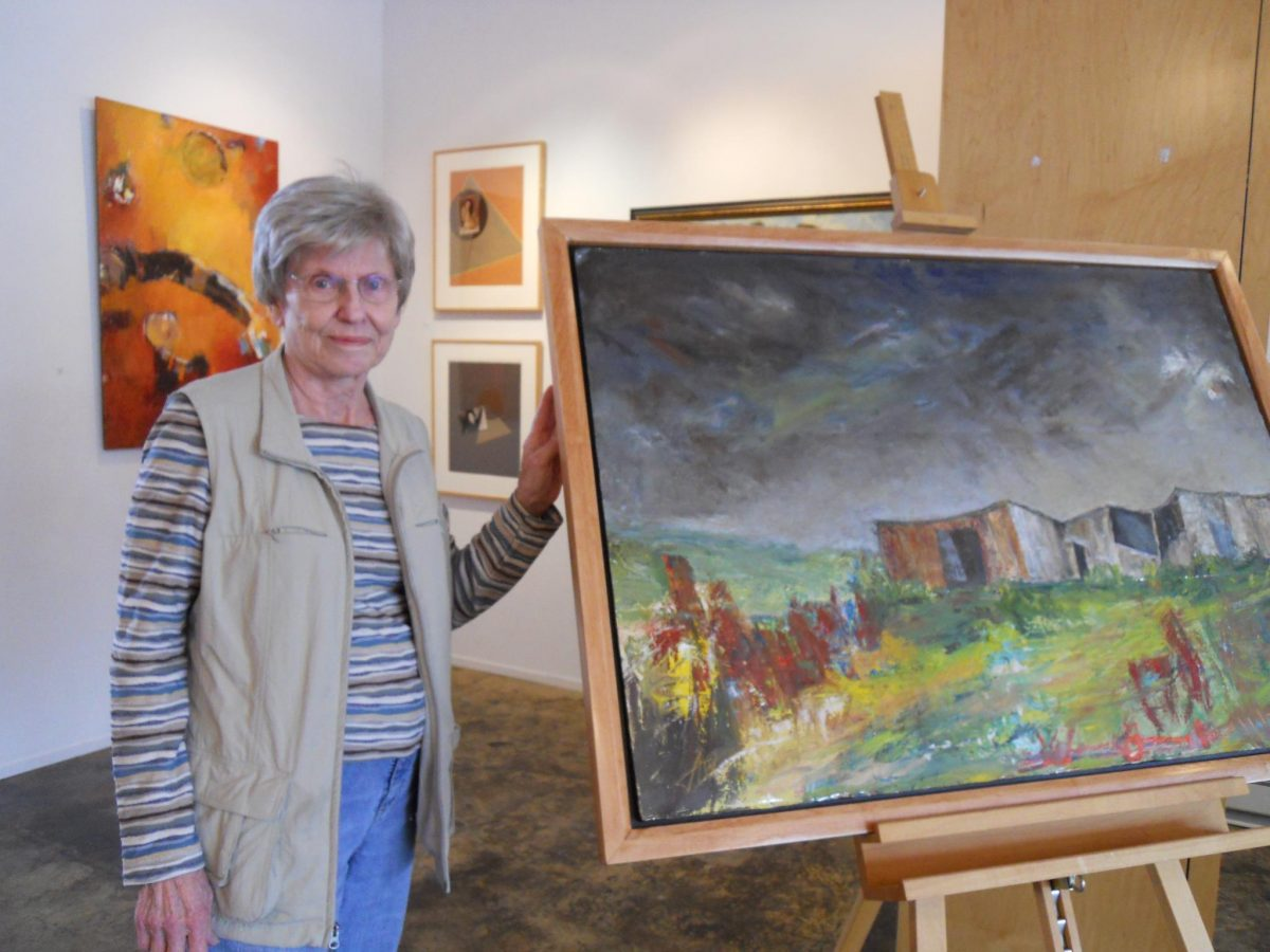 Artist Jane Woodworth poses with one of her original paintings.