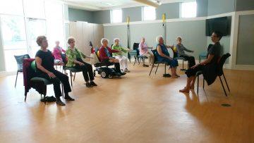 A chair yoga class at The Forest follows Cheryl's lead
