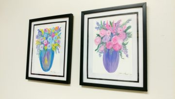 Two paintings by a self-taught artist hang in a hallway