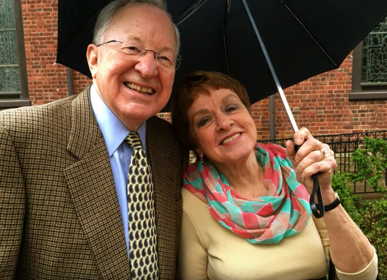 The Parrents smile together under an umbrella