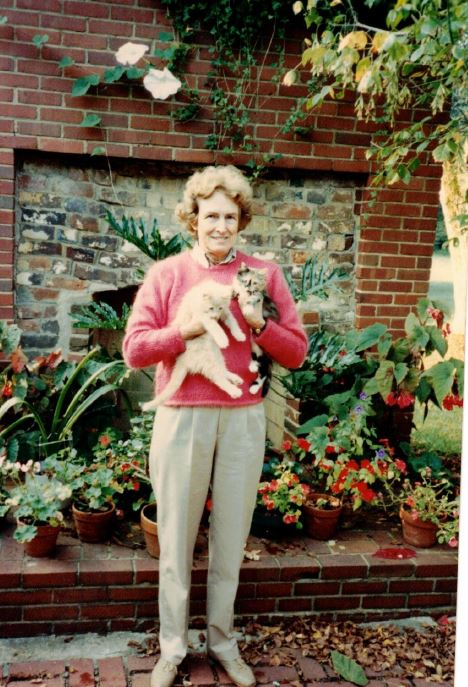 Jean Bradley Anderson stands on a terrace holding two kittens