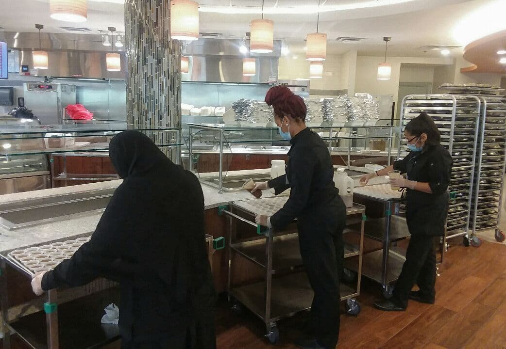 Dining team members fill condiment cups ahead of a meal.