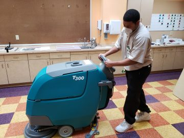 A Houseman cleans the floor during a pandemic.