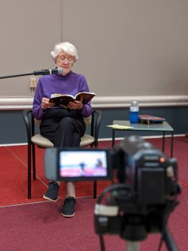 """A resident reads before a camera during a pandemic """"Resident Readers."""""""